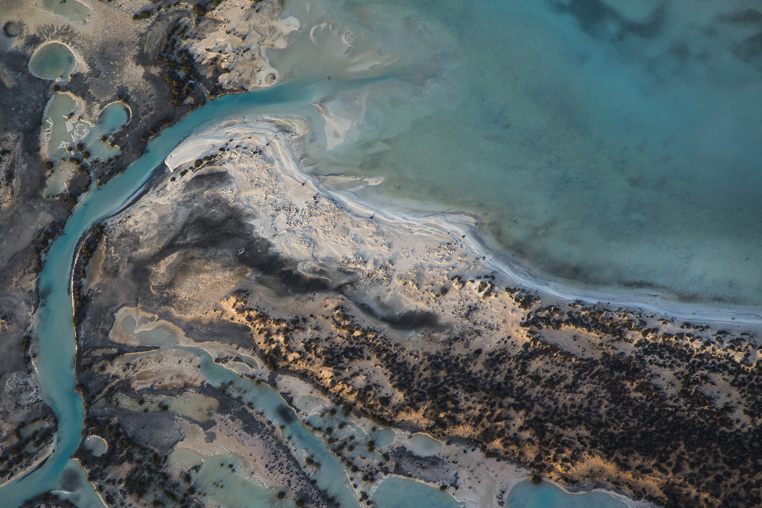 A horizontal abstract aerial photo of water taken in Australia in colour of blue, green and grey .