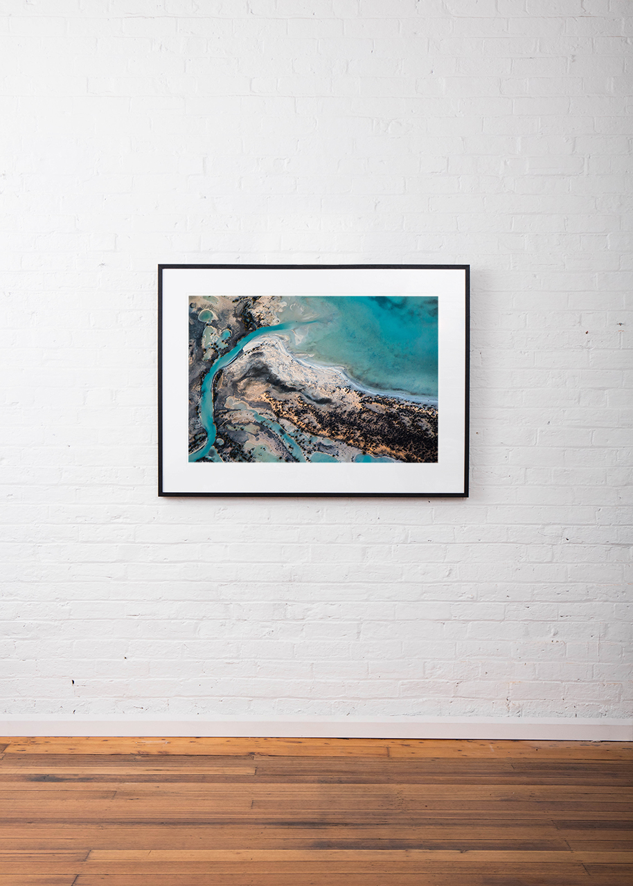 A horizontal abstract aerial photo of water taken in Australia in colour of blue, green and grey framed in black timber on white wall