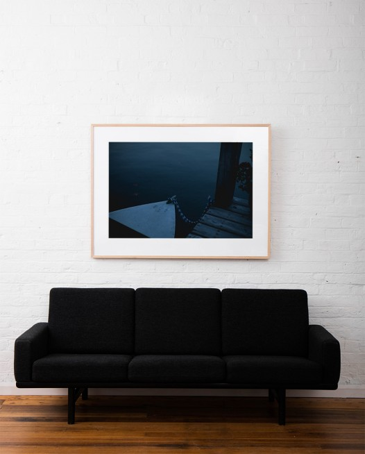 A horizontal Landscape photo of a boat tied to jetty framed in raw timber on white wall above sofa