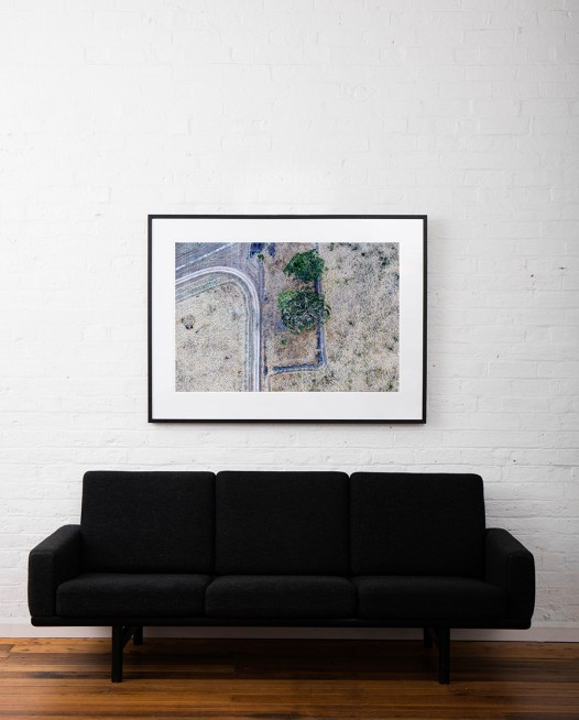 A Large Abstract Aerial photo of Australian Landscape of tress, road and paddocks framed in black timber on white wall above sofa