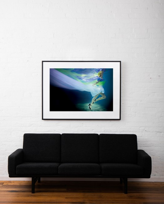 A large photographic art print of a girl under water in blue, green and purple framed in black timber on white wall above sofa