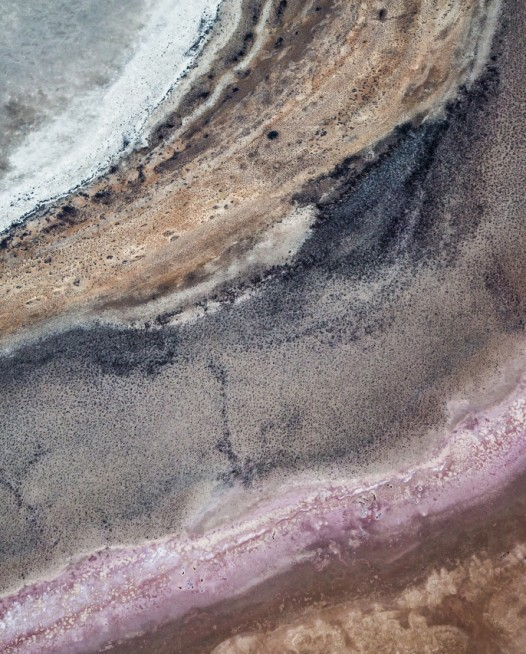 A horizontal abstract, aerial photo of Australia water in pink, purple, and red.