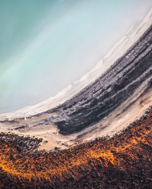 A horizontal abstract, aerial photo of sand and water in Australian Landscape in Orange, blue and brown.