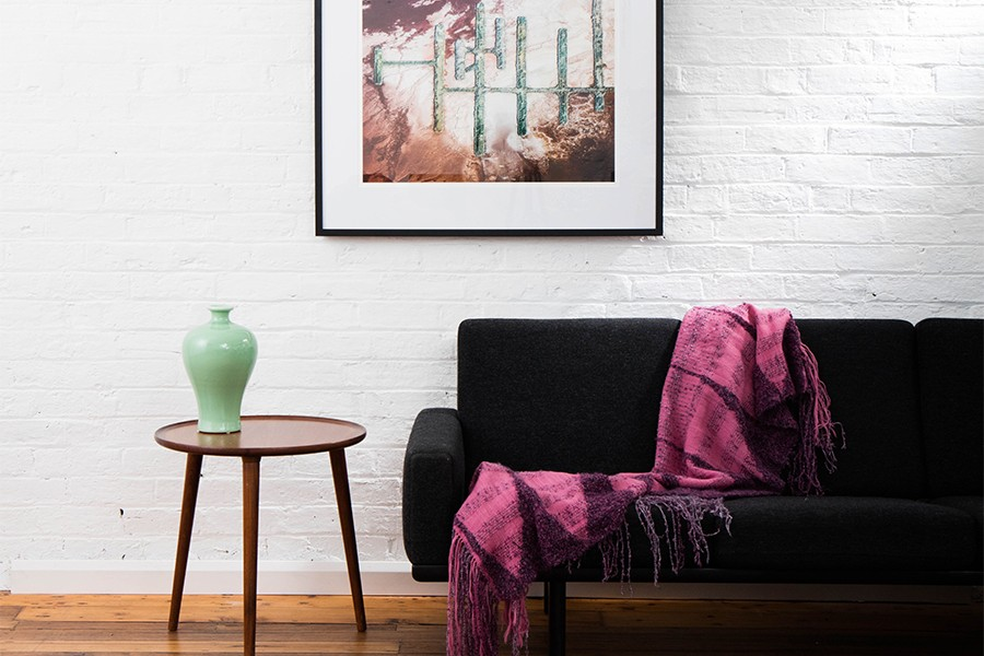 A Vertical Abstract Aerial photo of Australian Landscape in Pink, Purple and Red framed in dark timber in living room
