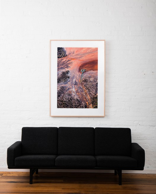 A Large Vertical Abstract Aerial Landscape photo of water in orange, pink, black and red taken in Australia framed in raw timber on white wall above sofa