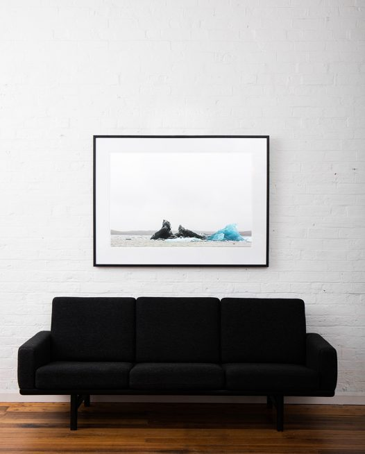 Large photographic art image of glacier, iceberg floating in water taken in Iceland Landscape. Framed in black timber on white wall above sofa