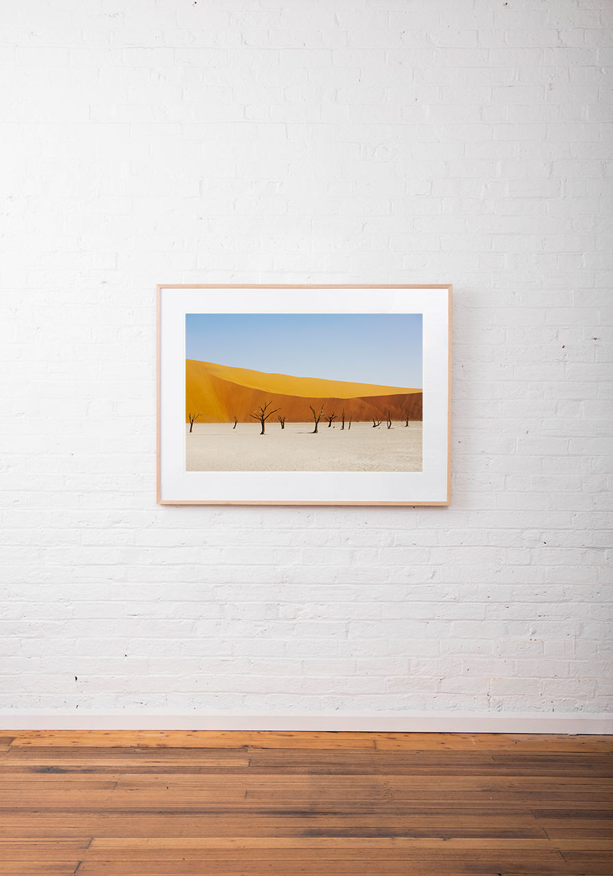 A abstract photo of Africa Landscape in yellow, gol and blue framed in raw timber on white wall