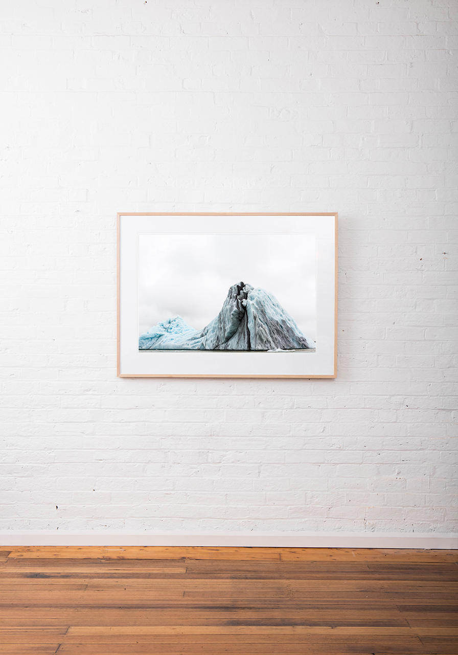 Large Blue and white Icelandic landscape of water, sky, glacier and snow. Framed in raw timber on white wall