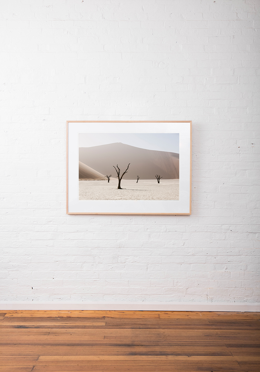 An Abstract photo of African Landscape of mountains, sand and trees in brown, pink and white framed in raw timber on white wall