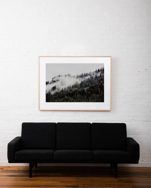 A photographic print of mist and fog over Mountains and trees in Canada framed in raw timber on white wall above sofa