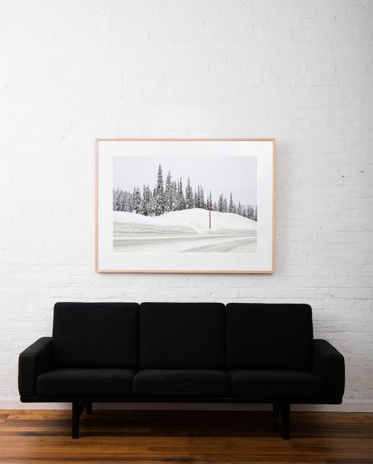 Large Photographic art print of a road with snow lined with trees taken in white Urban Landscape in Canada framed in raw timber on white wall above sofa