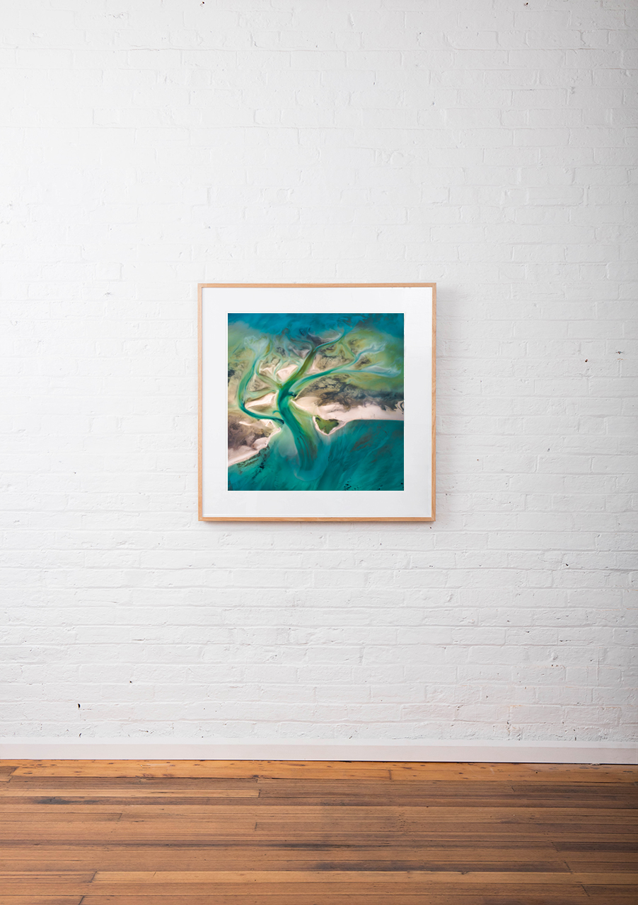 A Abstract Aerial Landscape of water in blue and green framed in raw timber hang on white wall