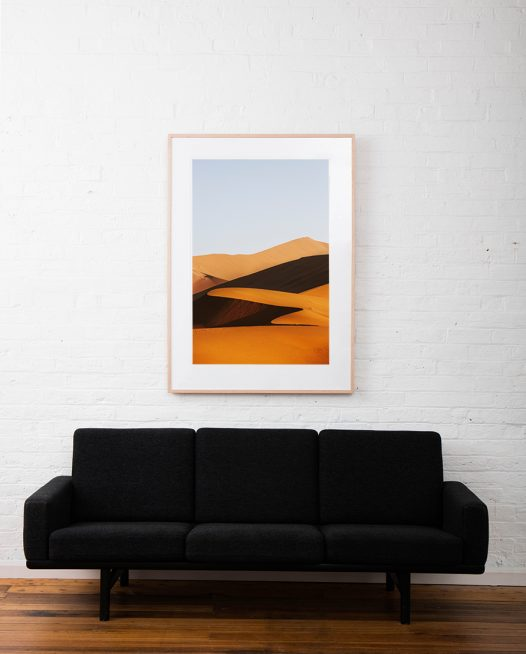 A large vertical abstract photo of African Sand Dunes framed in raw timber on white wall above sofa