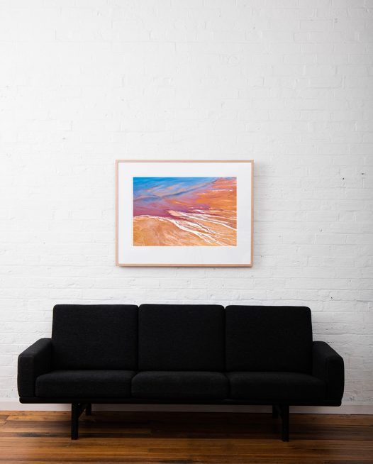 An Abstract Aerial Landscape photo taken in Shark Bay, Australia with splash of colour in orange pink and blue framed raw timber on white wall above sofa