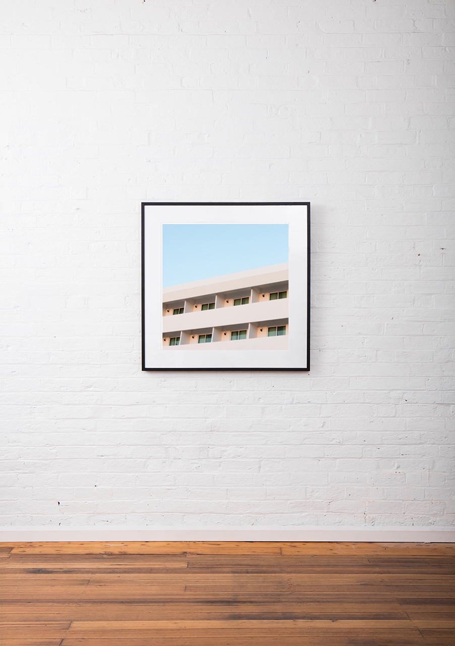 Architectural building taken by Eizabeth Bull in Central American Urban Landscape captured in Pink and Blue tone in a Modernism ernism Art Print framed in black timber square frame on white wall