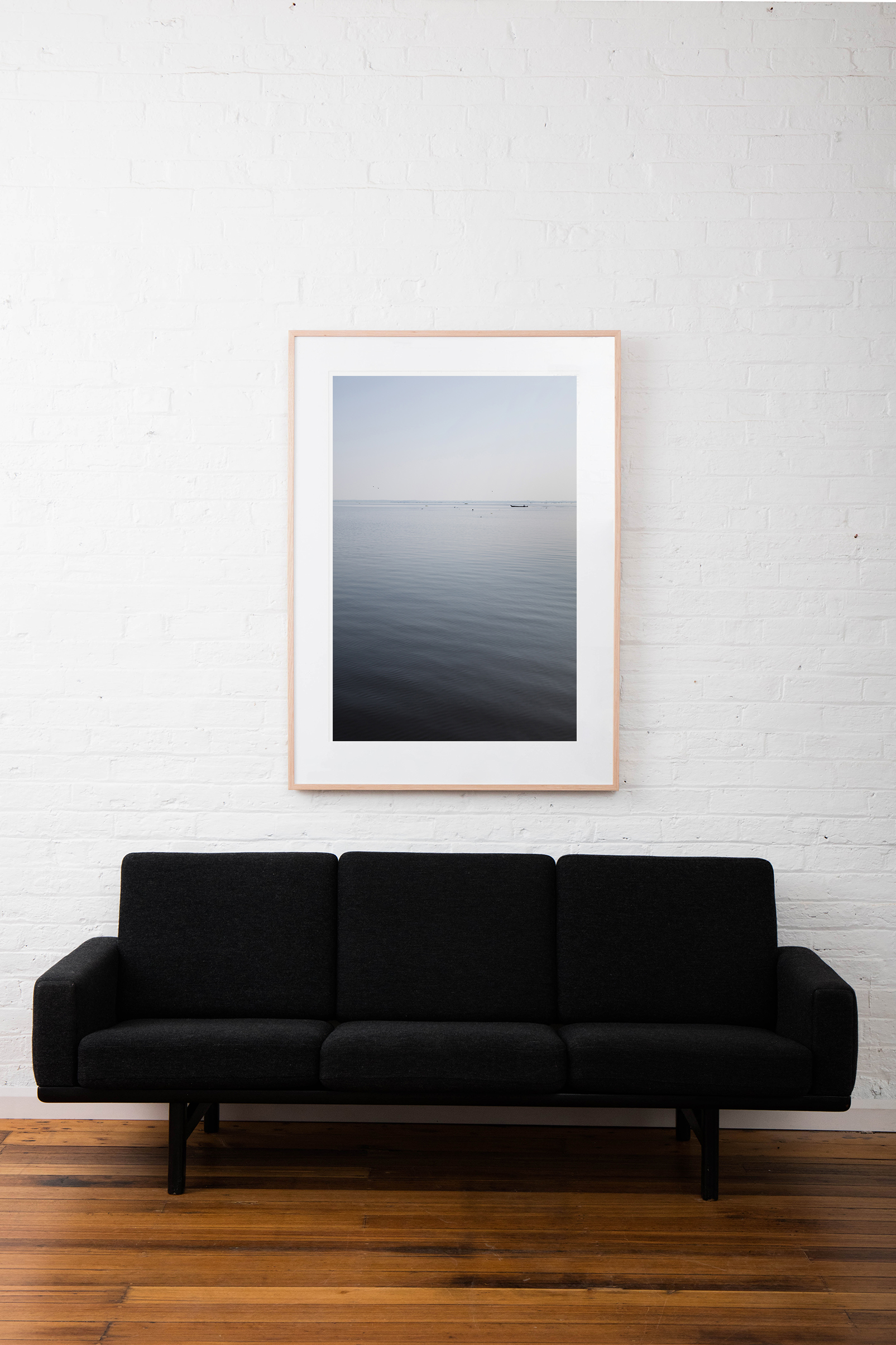 A large vertical abstract image of water - blue grey, taken in India Landscape by Elizabeth Bull framed on raw timber frame on white wall above sofa