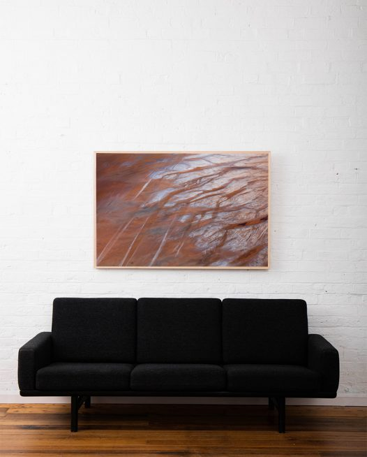 A large aerial photo of inland Australian landscape in brown orange and grey colours framed in raw timber above sofa
