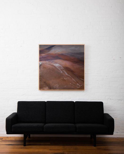 An areial photo of inland Australian landscape of brown, pink, orange, purple colour framed in raw timber above sofa