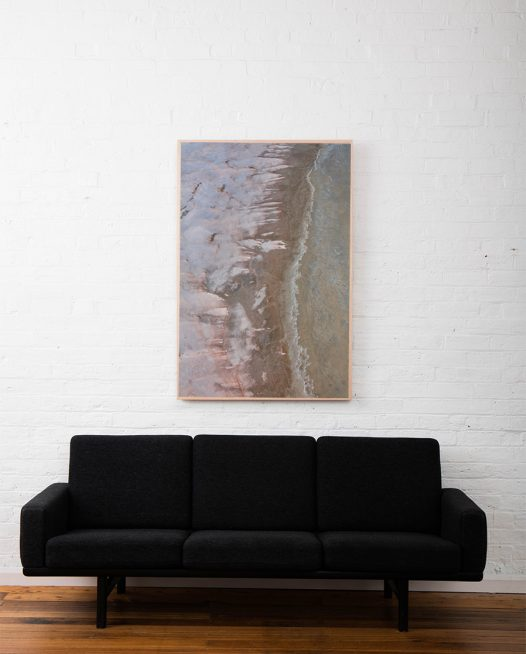 A large aerial photo of inland Australian landscape of pink, grey, brown and orange colour framed in raw timber above sofa