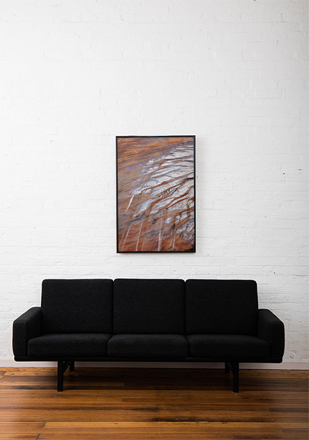 An aerial photo of inland Australian landscape in grey, brown and orange colour framed in black timber above sofa