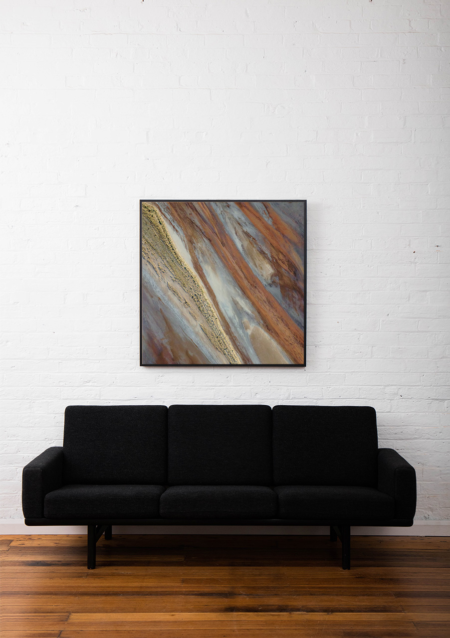 An aerial landscape photo of Australia in brown yellow and silvery colour framed in a black timber frame above sofa
